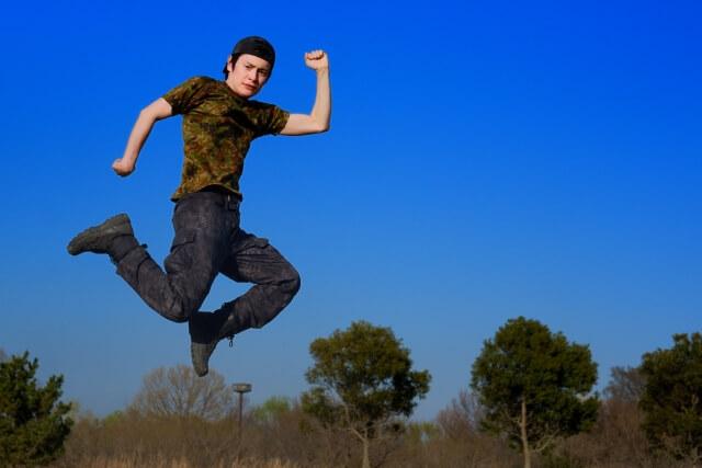 迷彩服を着た男性がジャンプ