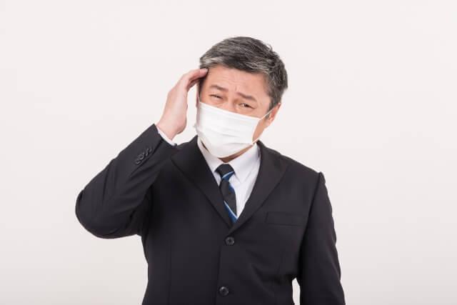 マスクをした男性が頭痛を訴える写真