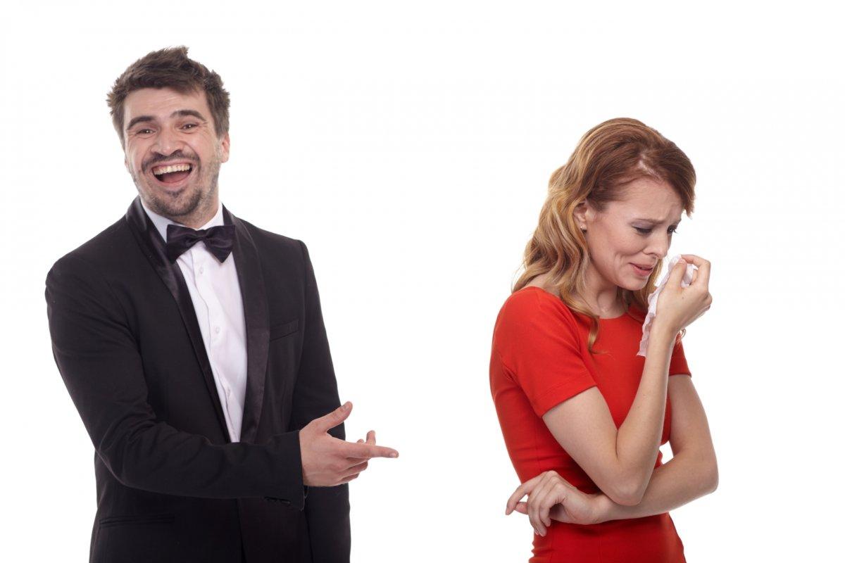 泣く女性に笑う男性