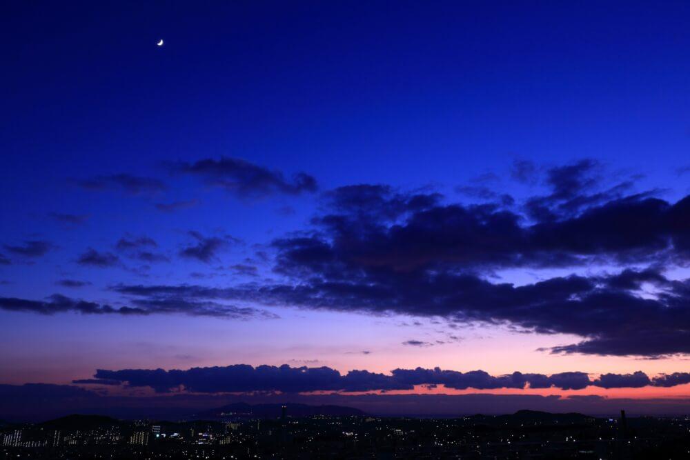 月と夕焼けの空の写真