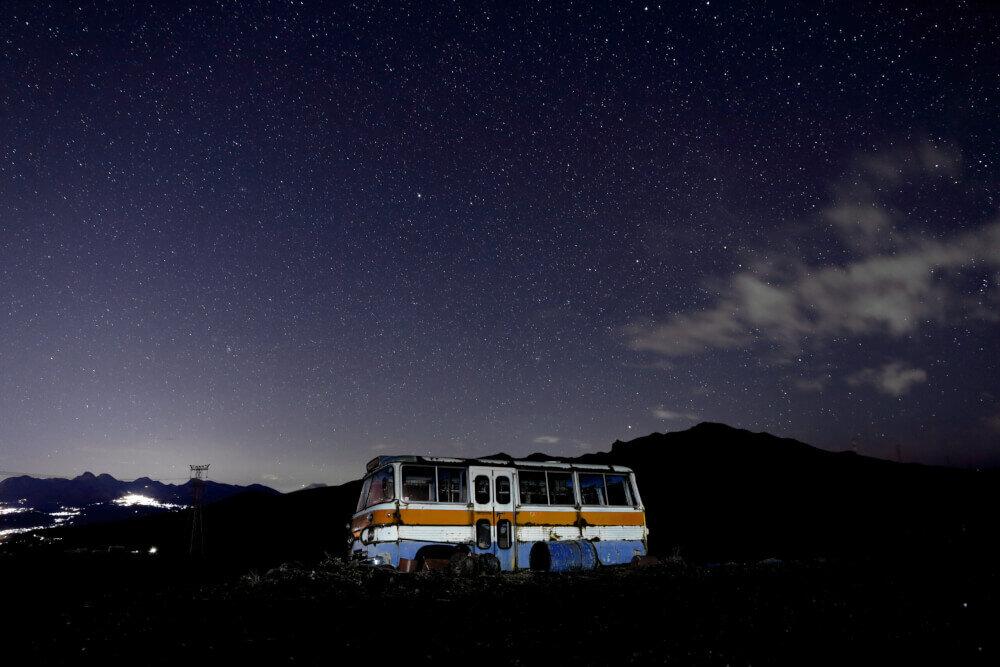 暗い場所に放置されたバスの写真