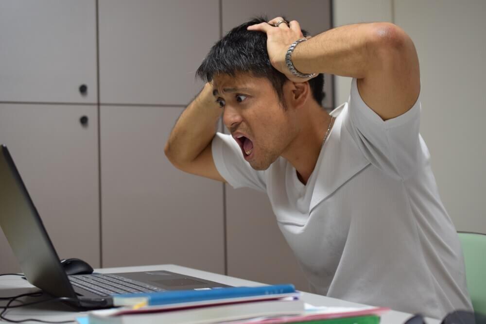 パソコンの前でビックリする男性